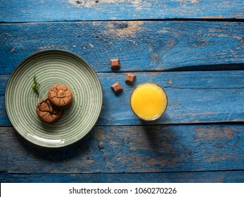 plate with bowny, fresh orange juce on blue painted plank table