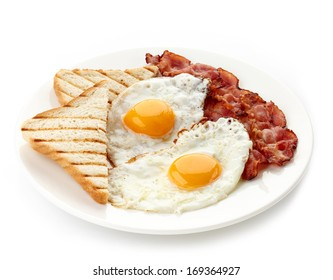 Plate of breakfast with fried eggs, bacon and toasts isolated on white background