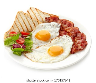 Plate of breakfast with fried eggs, bacon and toasts