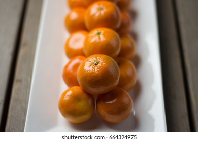 Plate of bright orange mandarins on a rustic table.