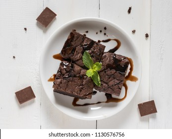 A plate of brownies with chocolate sauce on white wooden background, mint leaf on top, top view