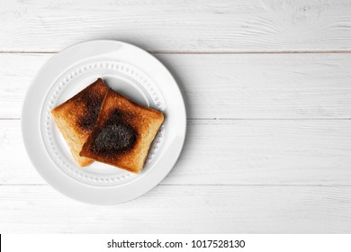 Plate with burnt toasted bread on light background