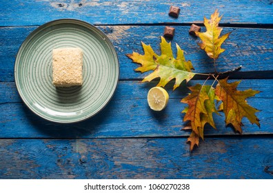 plate with cake, lemon and maple leaf on blue painted plank table