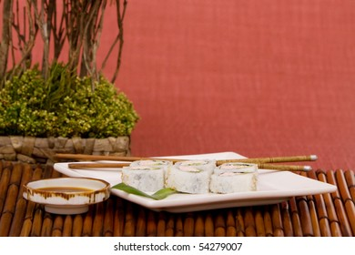 Plate of California rolls with soy sauce and chopsticks