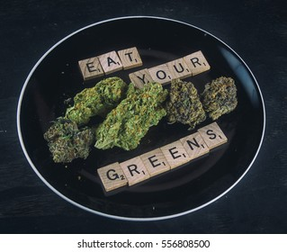 Plate with cannabis buds on black background - concept for infused medical marijuana food