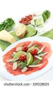a plate of carpaccio with parmesan, rocket and lime