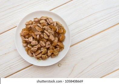 Plate with cat food (canned food) in a white saucer stands on a white wooden floor