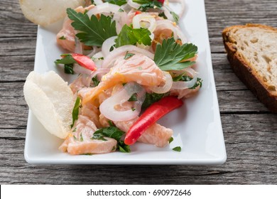 Plate with ceviche of salmon, onions, chili and parley