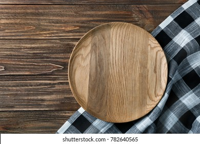 Plate and checkered kitchen towel on wooden table, top view