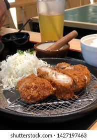 A plate of cheese chicken katsu with cabbage salad