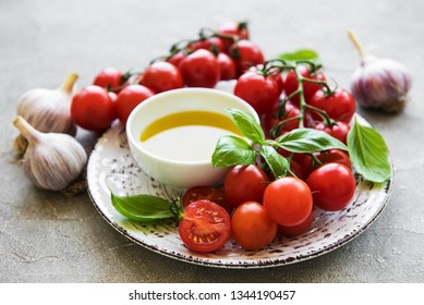 Plate with cherry tomatoes, olive oil and basil on a stone background