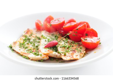 Plate with chicken breast with chives, cherry tomatoes and fresh whole chili