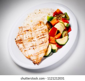 plate of chicken breast with rice and vegetables