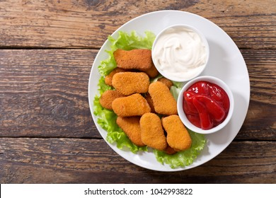 plate of chicken nuggets with sauces on wooden table, top view