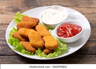 plate of chicken nuggets with sauces on wooden table