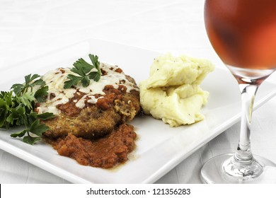 plate of chicken parmesan with mashed potatoes and red wine