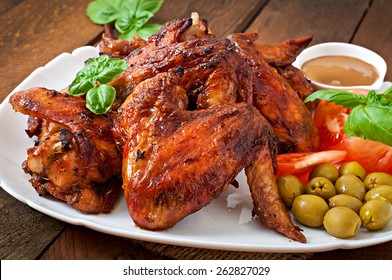 Plate of chicken wings on wooden background