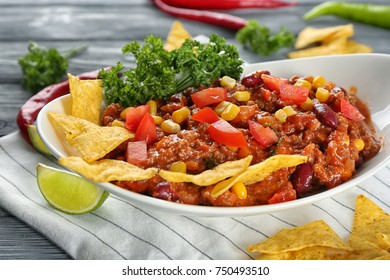 Plate with chili con carne and nacho chips on table, close up