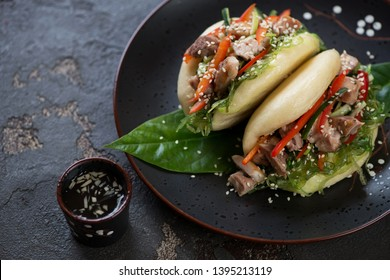 Plate with chinese traditional steamed gua bao, studio shot on a brown stone background, closeup