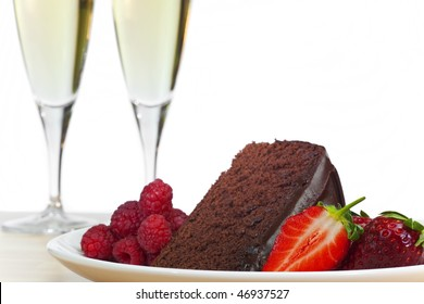 A plate of chocolate cake, raspberries and sliced strawberries with two flute glasses of champagne in the background.