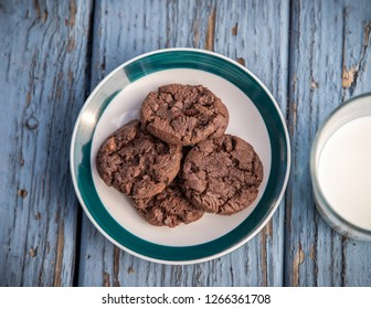 A plate of chocolate cookies on blue wooden floor
