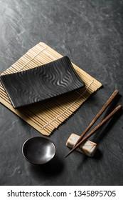 Plate, chopsticks on black table background