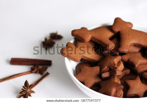 Plate of Christmas Gingerbread Cookies on White Background with Spices.