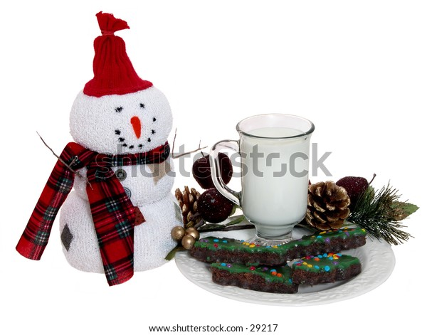 Plate of christmas tree shaped chocolate iced & sprinkled cookies and a glass of milk left for santa.  Surrounded by holiday decorations.