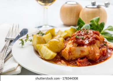Plate of Cod or Pollack Fillet Braised in Tomato and Thyme Sauce Garnished with Boiled New Potatoes