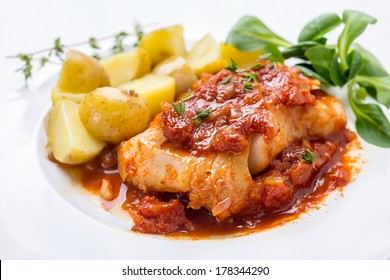 Plate of Cod or Pollack  Fish Fillet Stewed in Tomato and Thyme Sauce Garnished with Boiled New Potatoes