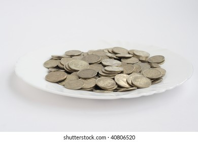 plate of coins isolated on white background