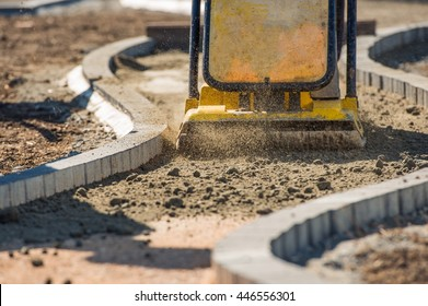 Plate Compactor in Action. Compacting Soil For a Brick Pavement.