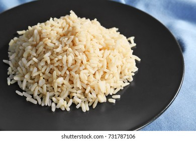 Plate with cooked rice on table