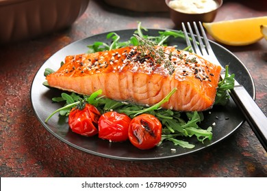 Plate with cooked salmon fillet on color background