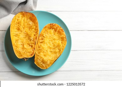 Plate with cooked spaghetti squash on white wooden background, top view. Space for text