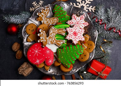 A plate with cookies around scattered holiday symbols on a stone background close-up