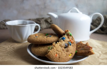 A plate of cookies with chocolate candy bits and a cup of tea and teapot.