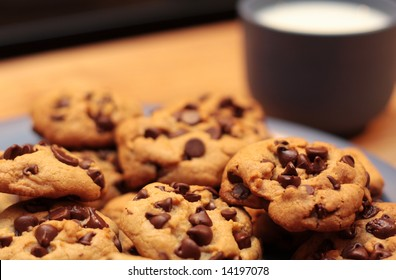 A plate of cookies with a cup of milk in the background