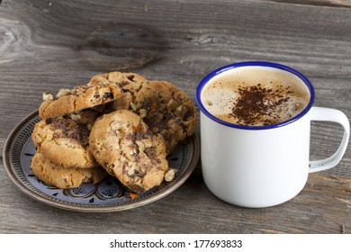 Plate of cookies and a Enamel Mugs with coffee on a rustic wooden board with Copy Space on the Coffee Cup