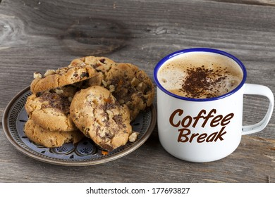 """Plate of cookies and a pot of coffee with the word """"Coffee Break"""" on a rustic wooden board"""