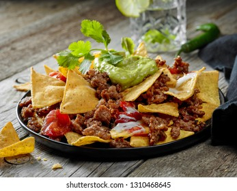 plate of corn chips nachos with fried minced meat and guacamole on wooden kitchen table