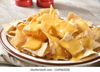 A plate of corn tortilla chips with creamy cheese sauce.