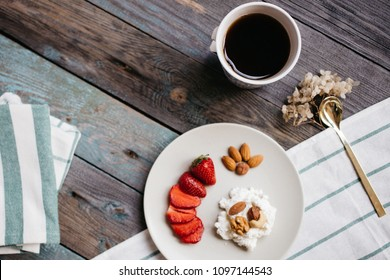 a plate with cottage cheese, strawberries and nuts, a cup of coffee and towels on a wooden table, healthy food, breakfast