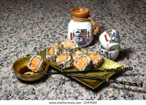 Plate of crab sushi, chop sticks and sake cups on a granite counter