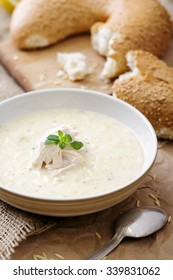 a plate of cream soup with a piece of meat and some bread on a cutting board on the background
