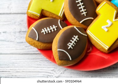 Plate with creative cookies decorated in football style, closeup