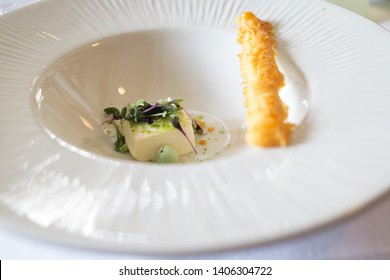 Plate with creme fraich cube and cheese bread stick.
