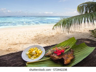 Plate of creole food with fish and mango salad on Seychelles Islands, Anse Source D'argent beach / Red Snapper fish with mango salad on a palm tree leaves, traditional creole food