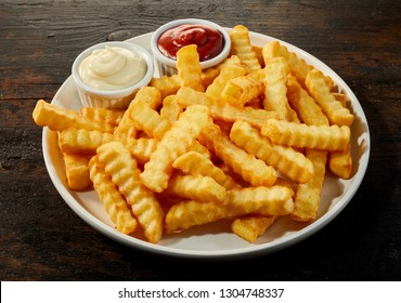 Plate of crinkle cut crisp golden French fries with mustard, mayonnaise and ketchup dips for a menu on dark wood