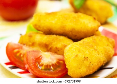 Plate of croquettes with lettuce and tomato